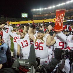 Wisconsin Badgers team hold up the Paul Bunyan Axe after defeating the Minnesota Golden Gophers