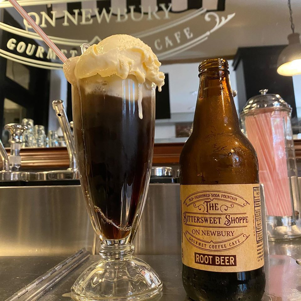 A root beer float in a glass sits next to a bottle of root beer with a straw dispenser visible in the back