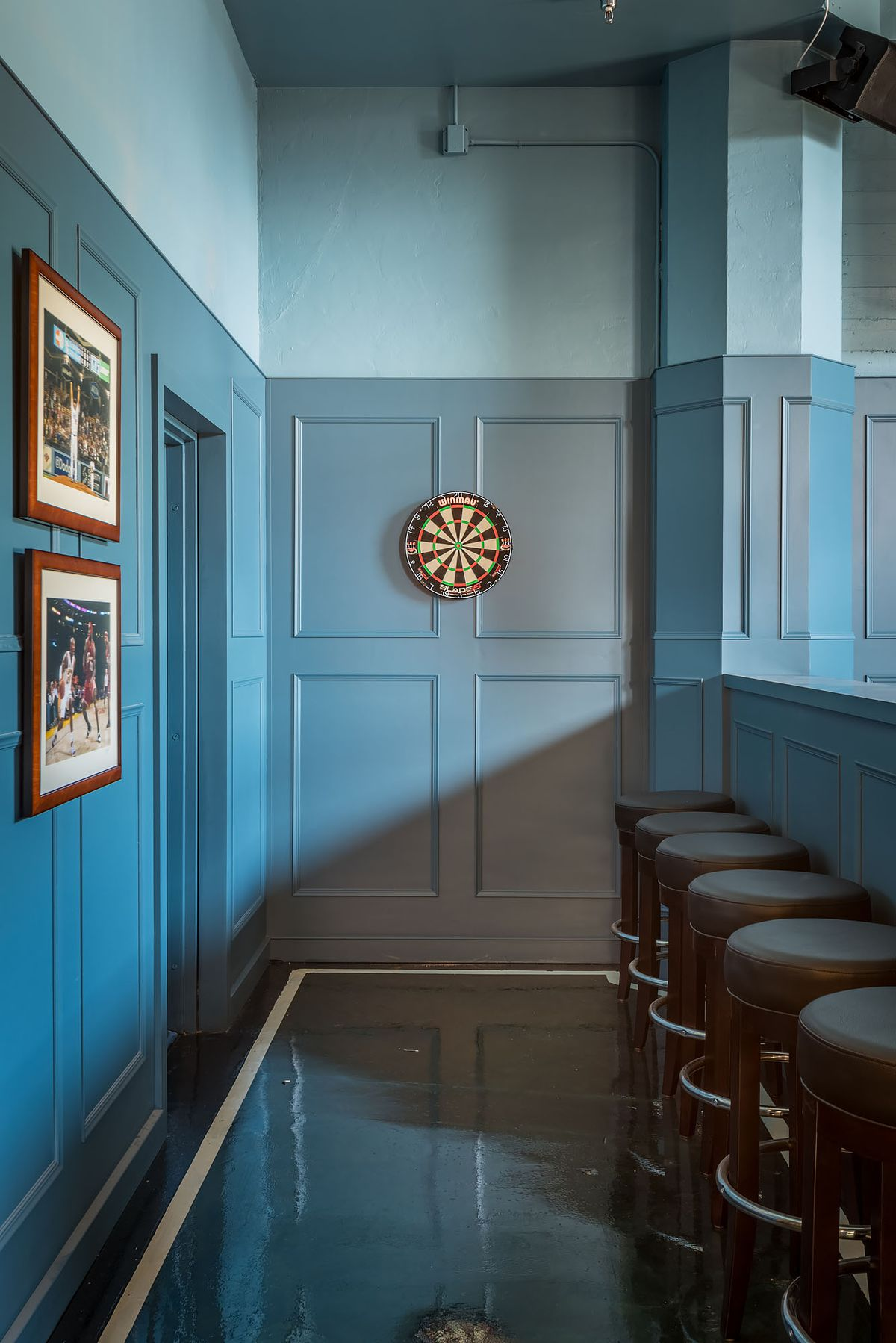 Dartboard with blue walls and barstools to the side.