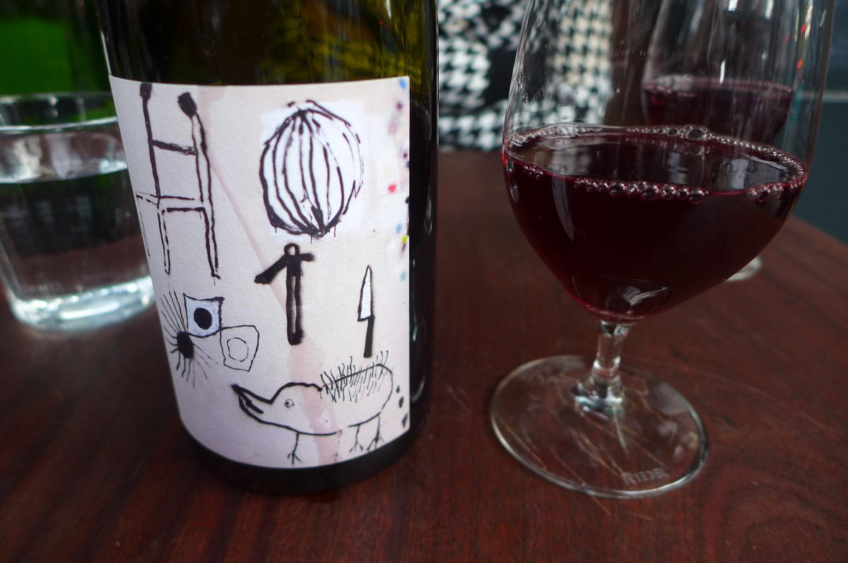 A bottle of red wine with a cartoony black and white label and a glass poured out on the side.
