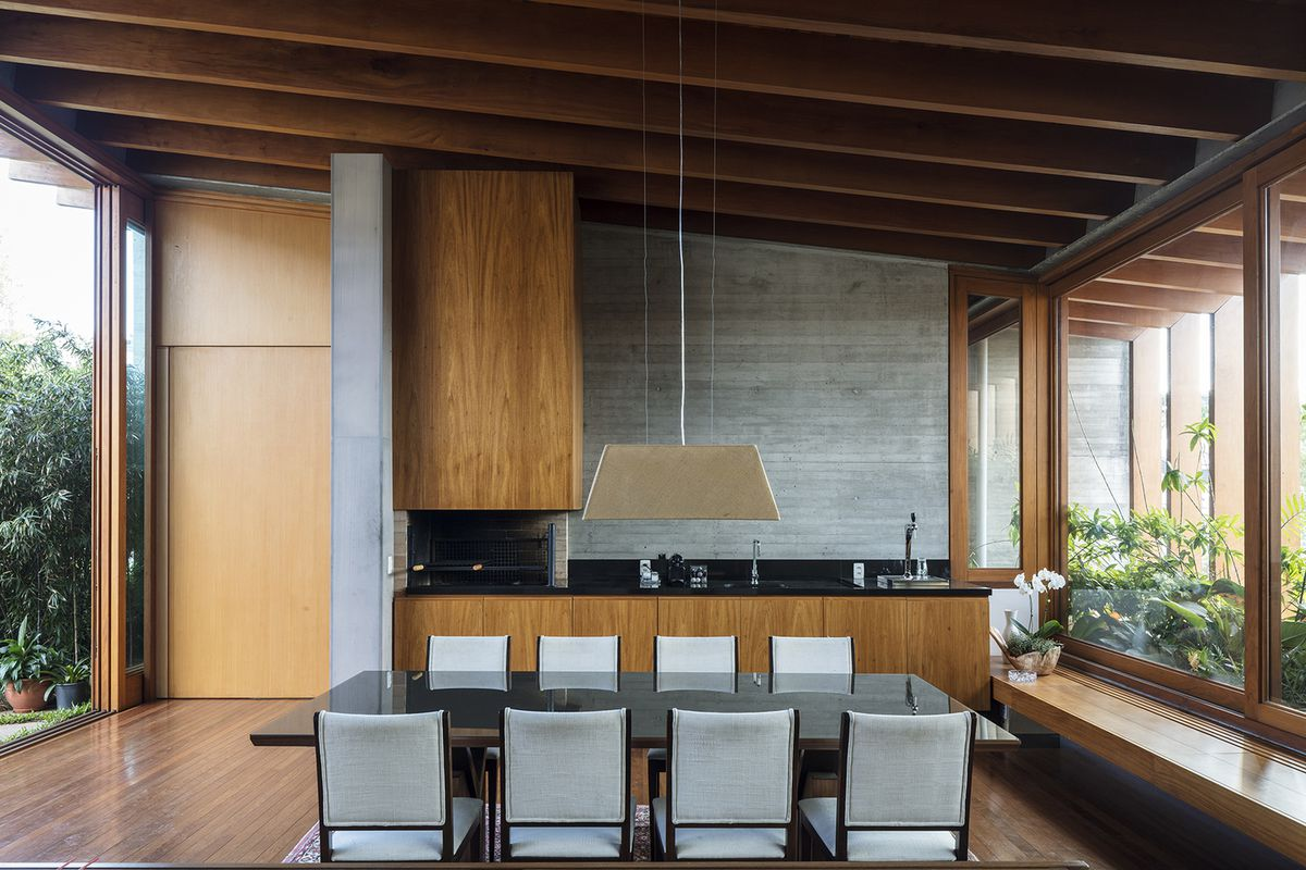 A modern wood and black kitchen with a slanted timber roof.