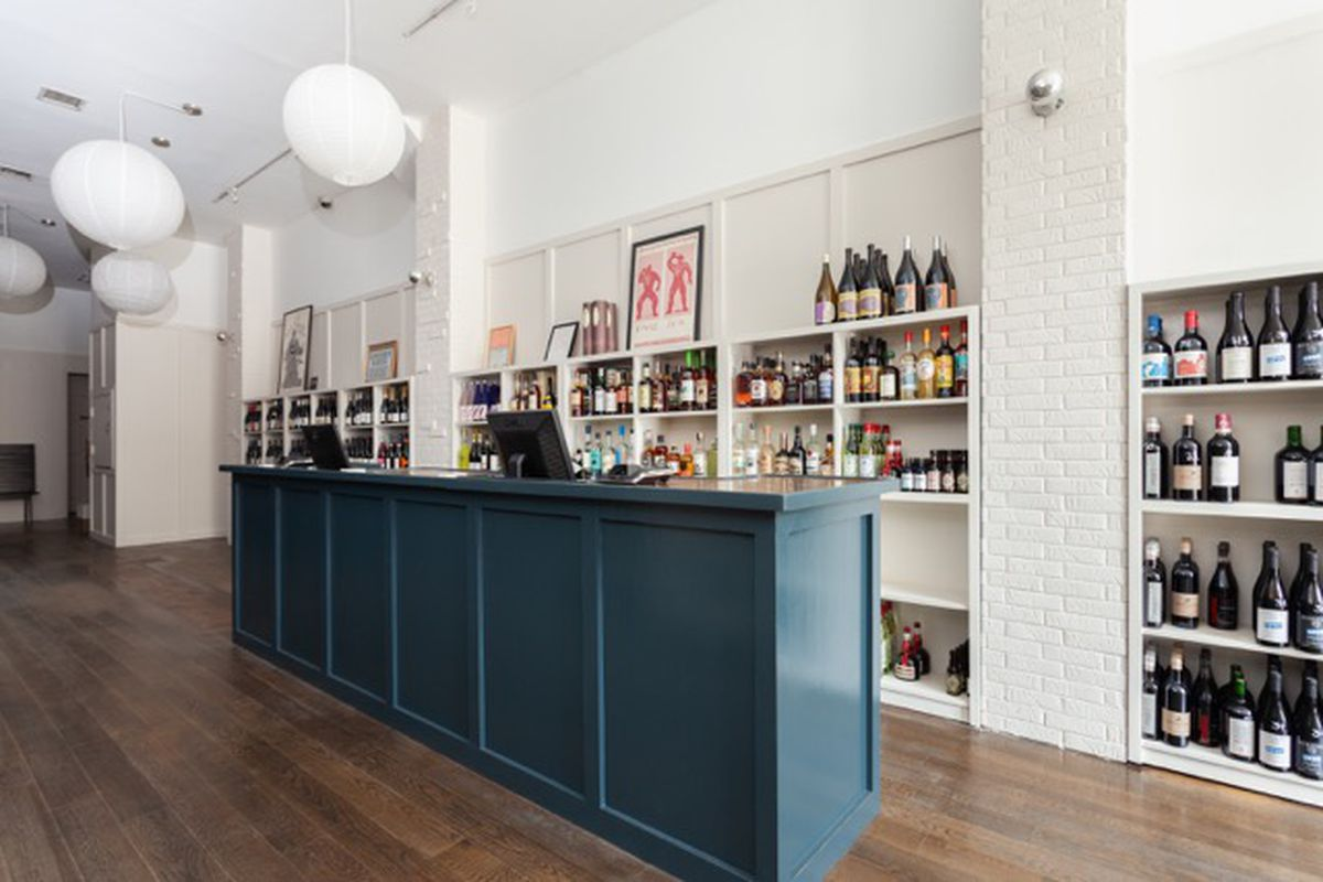 A wine shop with a white wall lined with bottles of wine with a blue counter in front of them