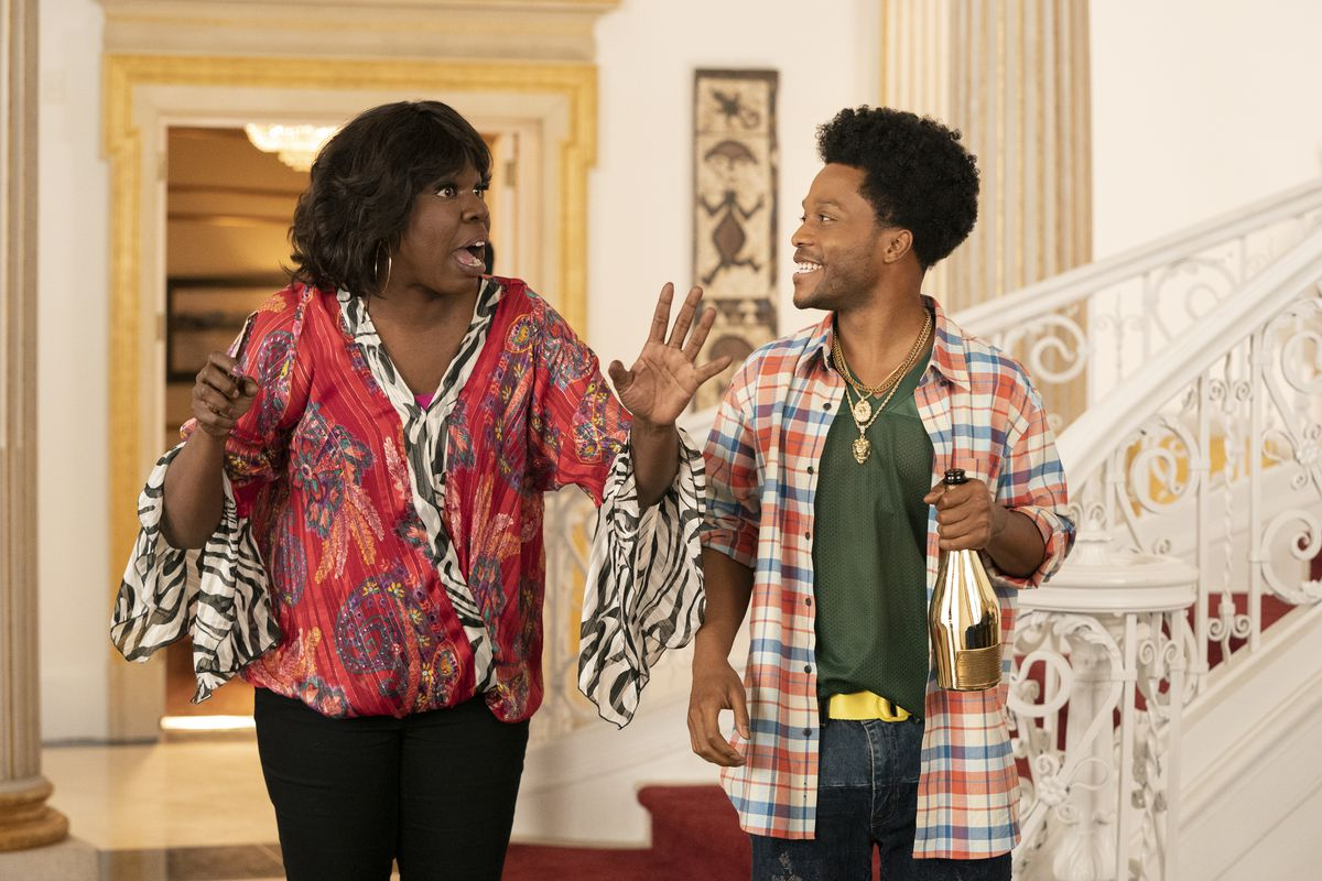 Leslie Jones and Jermaine Fowler stand at the base of an elaborate staircase in Coming 2 America