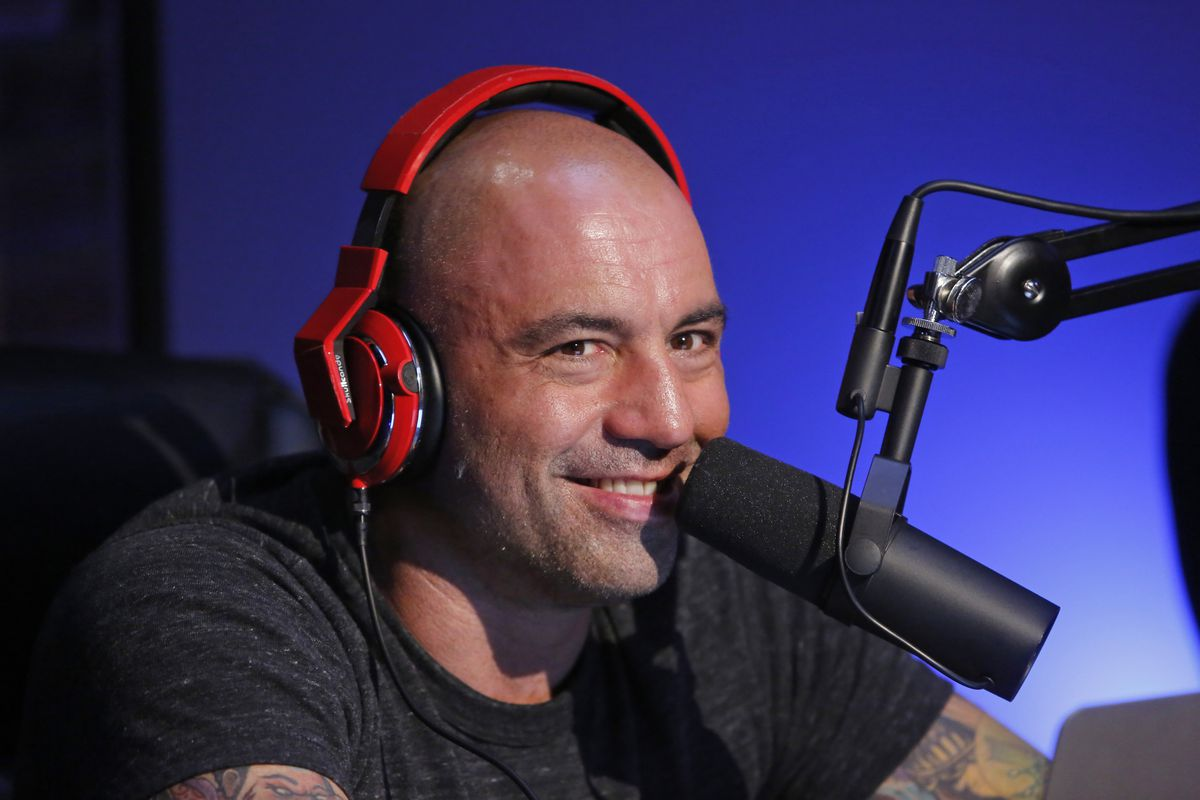 Podcaster Joe Rogan wearing headphones and smiling in front of a recording microphone.