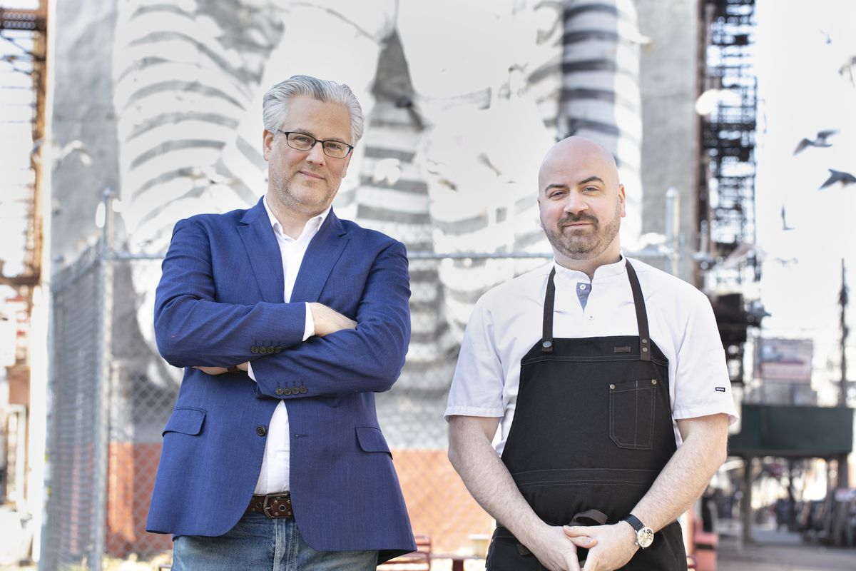 John Winterman in a blue suit and chef Chris Cippolone in a chef's apron