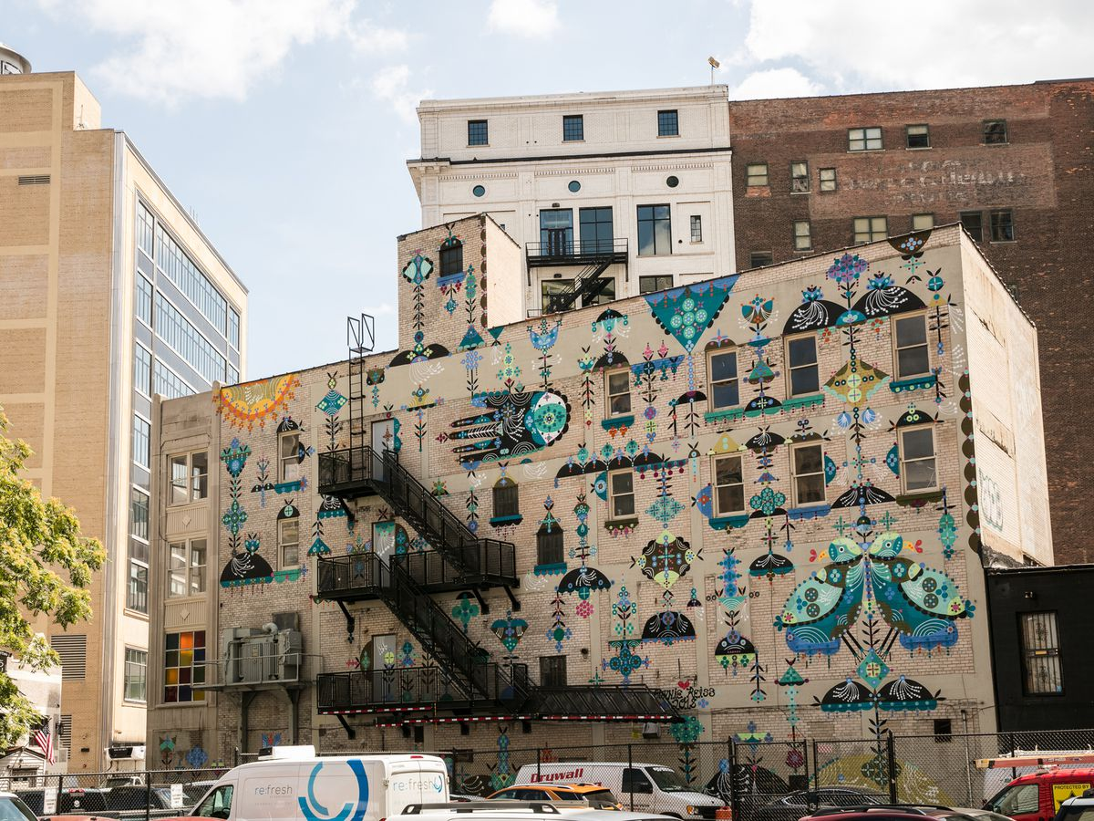 A large tan building with various murals of folklore symbols painted on the side of it.