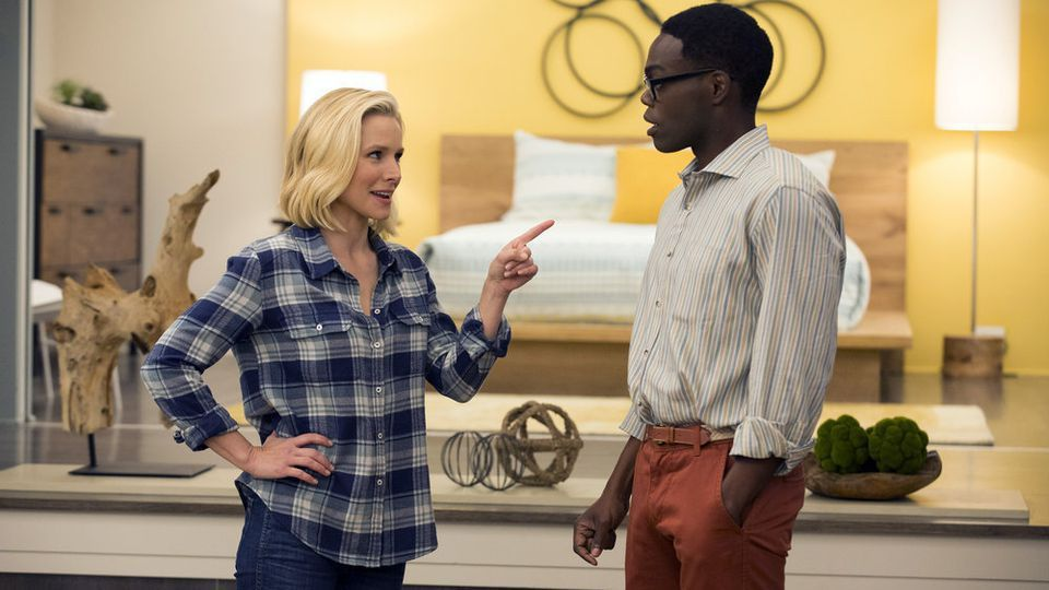 Two characters from the Good Place talk in front of a platform bed and sleek bedroom.