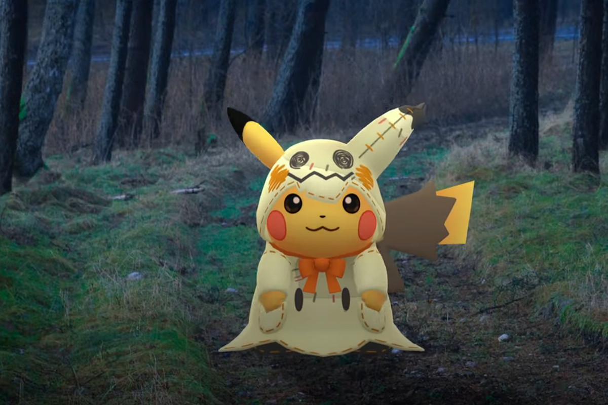 A Pikachu wearing a Mimikyu costume stands in a spooky forest.