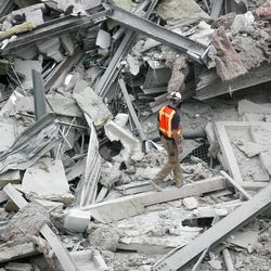A worker walks on the rubble after the old Key bank building was demolished in downtown Salt Lake City by explosives. August 17, 2007.