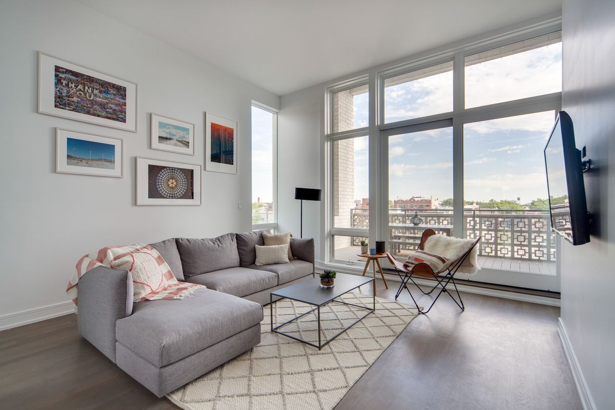 A sparse, minimalist living room in New York City with grey couches, a television set, and windows looking over the city skyline.