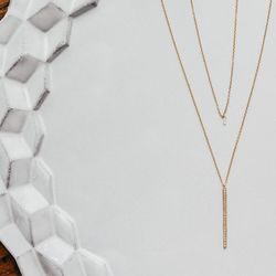 """The <a href=""""http://satomikawakita.com/collections/necklace/products/n1210w"""">Diamond Drop Necklace</a> ($705) and the <a href=""""http://satomikawakita.com/collections/necklace/products/n1209w"""">Diamond Bar Necklace</a> ($1,275)"""