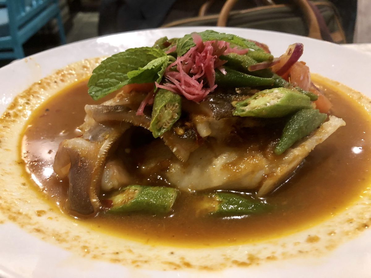 Fish head, okra, red onions, and mint in an orange sour curry sauce