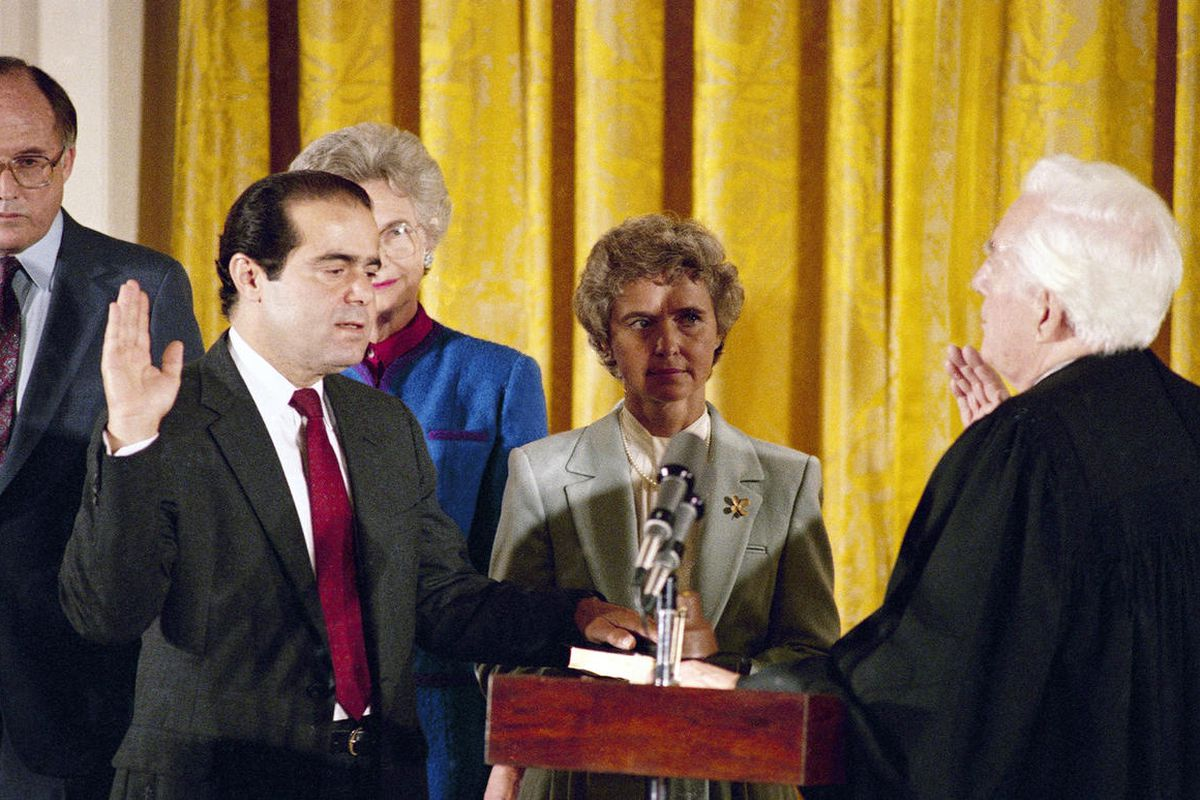 Retiring Chief Justice Warren Burger, right, administers an oath to Associate Justice Antonin Scalia, as Scalia's wife Maureen holds the bible during ceremonies in the East Room of White House, Washington on Friday, Sept. 26, 1986. Scalia is the 103rd per