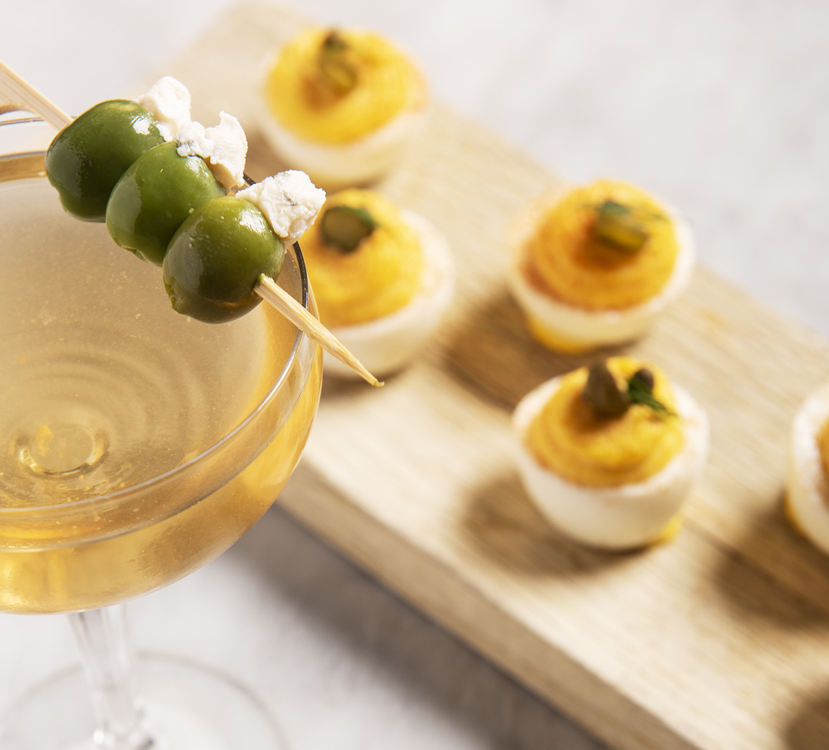 Four deviled eggs and a martini with three olives
