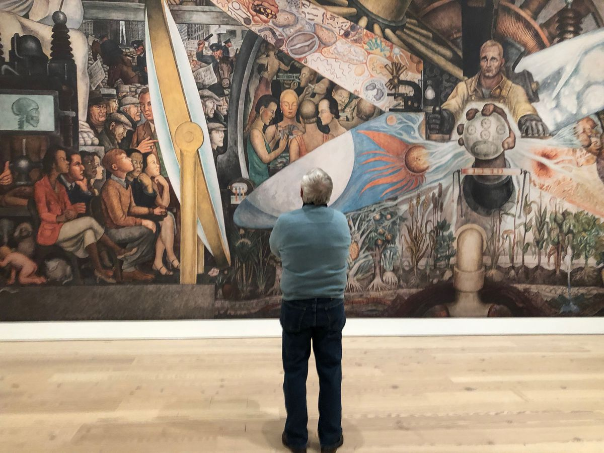 "A visitor at the Whitney Museum in New York contemplates a reproduction of ""Man, Controller of the Universe,"" by Diego Rivera."
