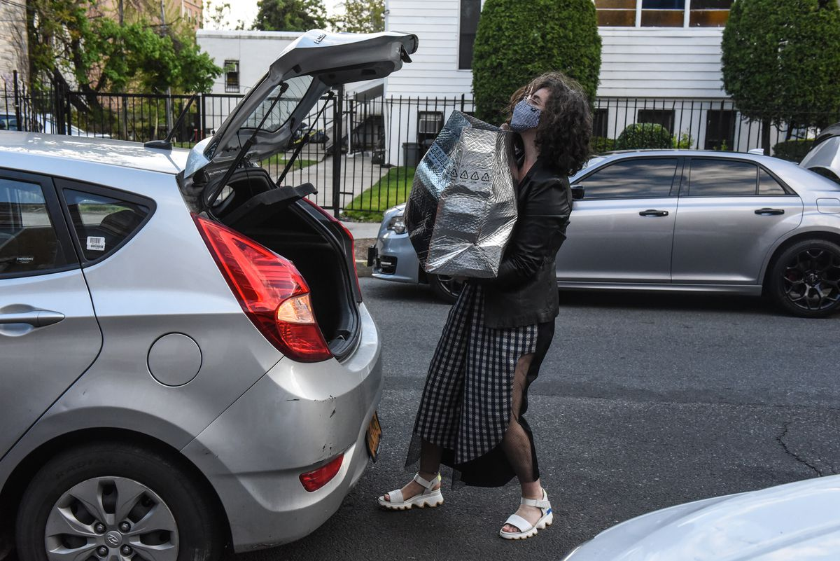 A woman wearing a face mask takes a large shopping bag out of the trunk of her car
