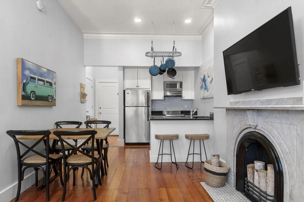 A small open kitchen-dining room area with a table and chairs across from a marble fireplace with a TV above it.