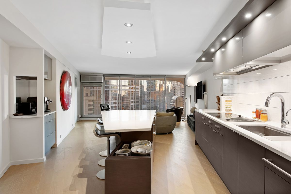 An open condo with a kitchen with dark cabinets and a pie-shaped white island breakfast bar with three stools. There is a living room and balcony beyond.