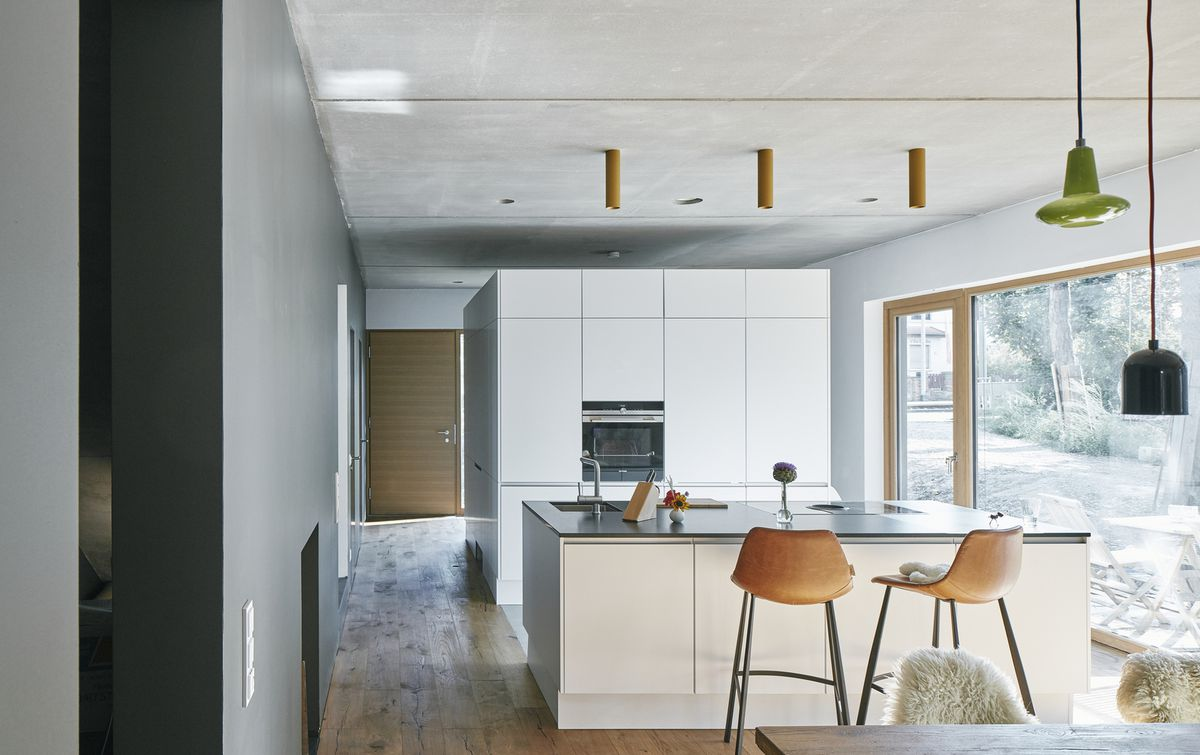 Open-plan kitchen with large breakfast bar and white cabinets.
