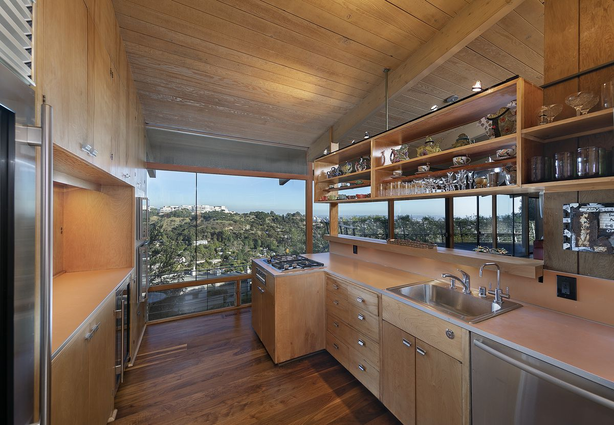 The galley kitchen has sleek wood cabinets, open shelving, stainless steel appliances, and wood beamed ceilings. At one end, walls of glass look out to hills and the Getty Center.