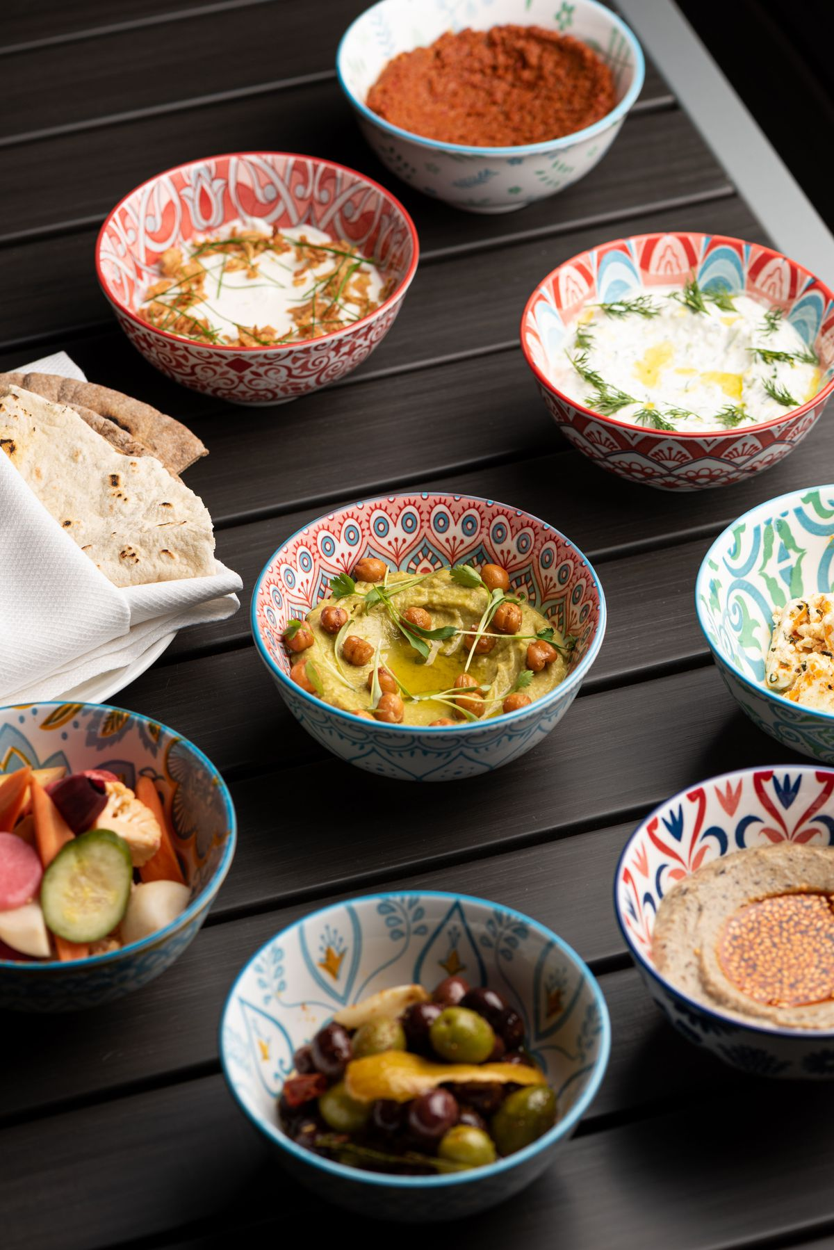 A from the side look at small bowls of mezze on a patio taboe.