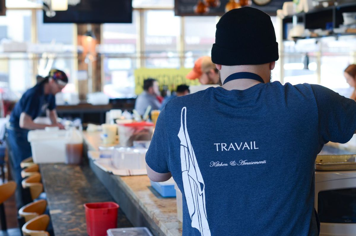 A cook with their back to the camera is wearing a blue Travail t-shirt inside the Robbinsdale restaurant