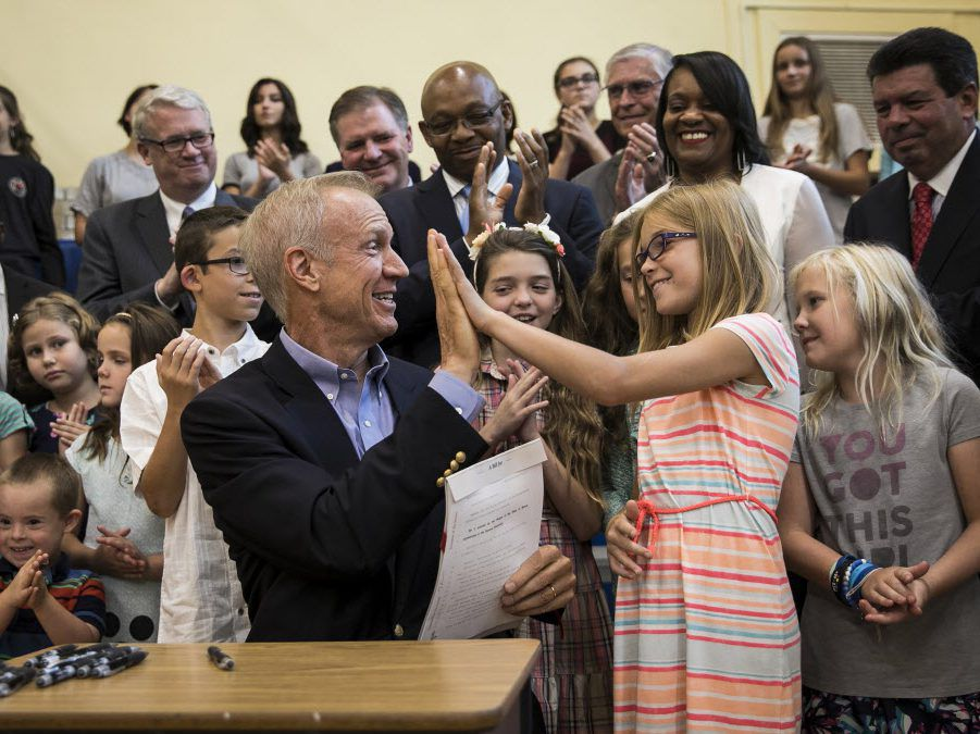 Gov. Bruce Rauner gives a student a high five after signing an education funding reform bill at Ebinger Elementary School on Aug. 31, 2017. File Photo. | Ashlee Rezin/Sun-Times