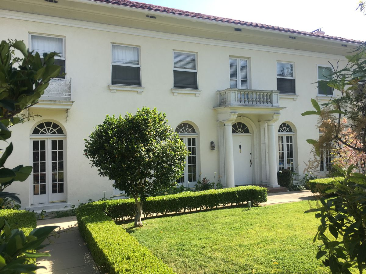 The exterior of the Joan Didion House in Los Angeles. The facade is white with columns on both sides of the front door.