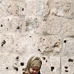 A Muslim girl reads from the Quran during noon prayers at mosque in Jerusalem's Old City.