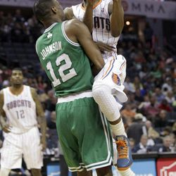 Charlotte Bobcats' Kemba Walker, right, runs into Boston Celtics' JaJuan Johnson (12) during the first half of an NBA basketball game in Charlotte, N.C., Sunday, April 15, 2012. Johnson was called for a foul.
