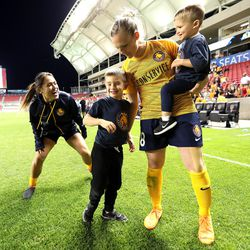 Utah Royals FC forward Amy Rodriguez (8) gathers her sons Ryan and Luke as teammate Lo'eau LaBonta (9) plays with them after a match against the Orlando Pride at Rio Tinto Stadium in Sandy on Wednesday, May 9, 2018.