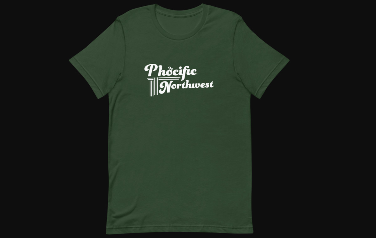 """A green t-shirt that says """"Phocific Northwest"""" against a black background"""