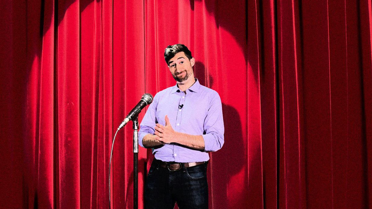 Scott Rogowsky standing on a stage next to a mic
