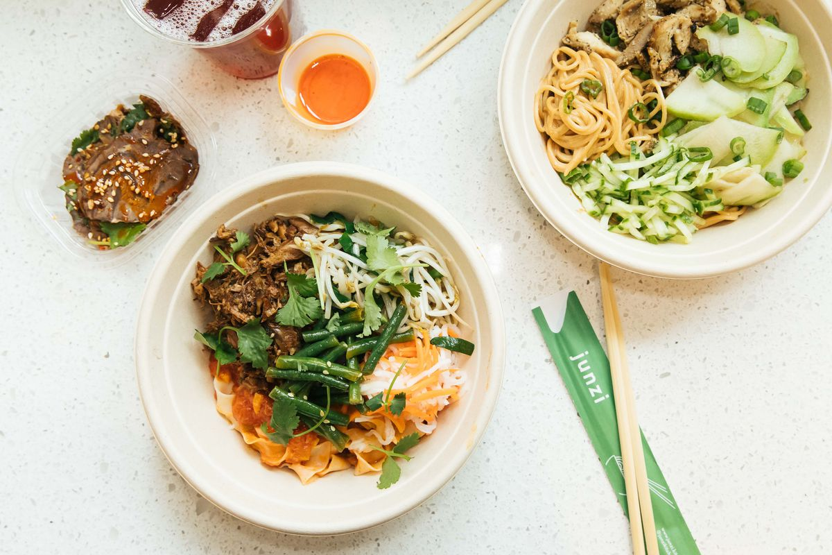 An overhead shot of bowls of noodles with accompaniments at Junzi Kitchen.