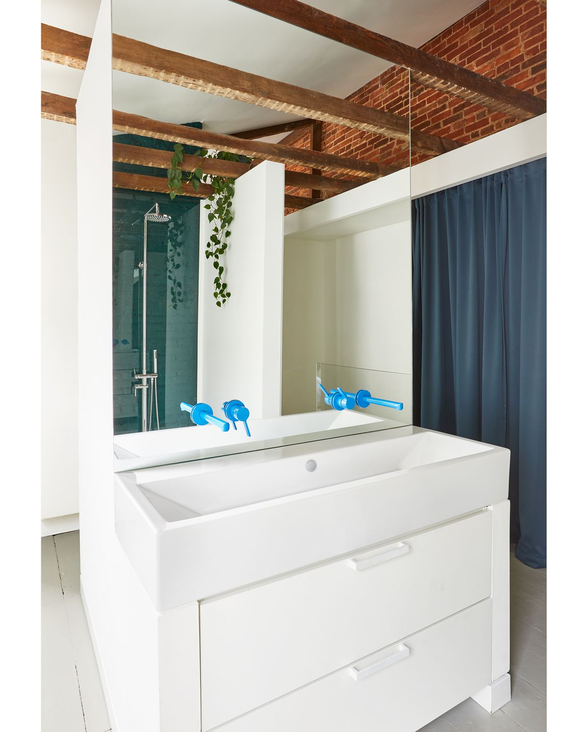 A bathroom. There is a white sink with storage drawers underneath. Above the sink is a mirror. Protruding from the mirror are blue faucet fixtures. The ceiling has exposed wooden beams and there is exposed red brick along the top of the walls.