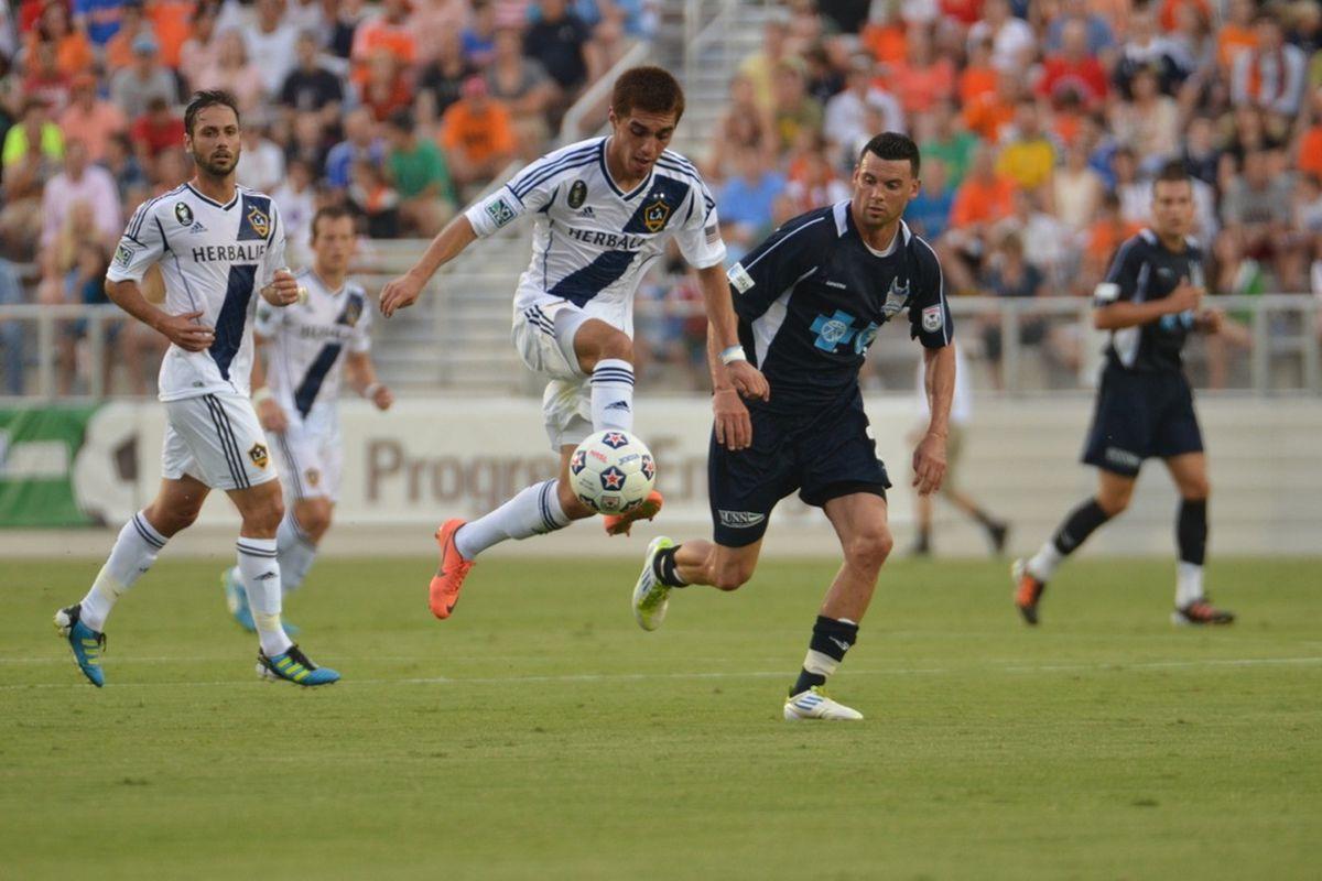 LA Galaxy's Hector Jinenez controls the ball with Pat Noonan looking on. Photo credit: Carolina RailHawks