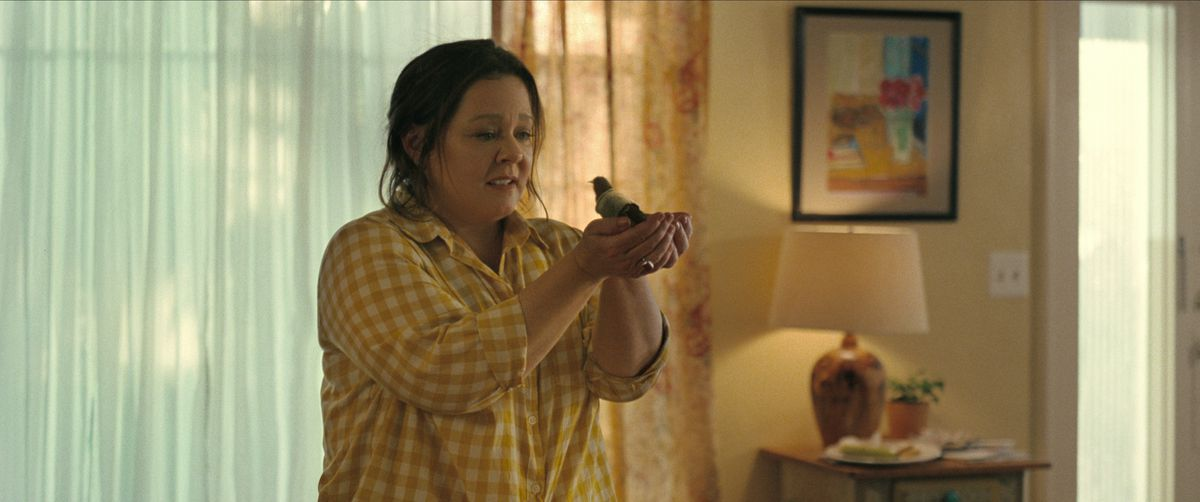 Melissa McCarthy holding a bird in her hands in The Starling