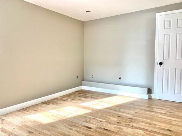 An empty bedroom with a closed closet door.