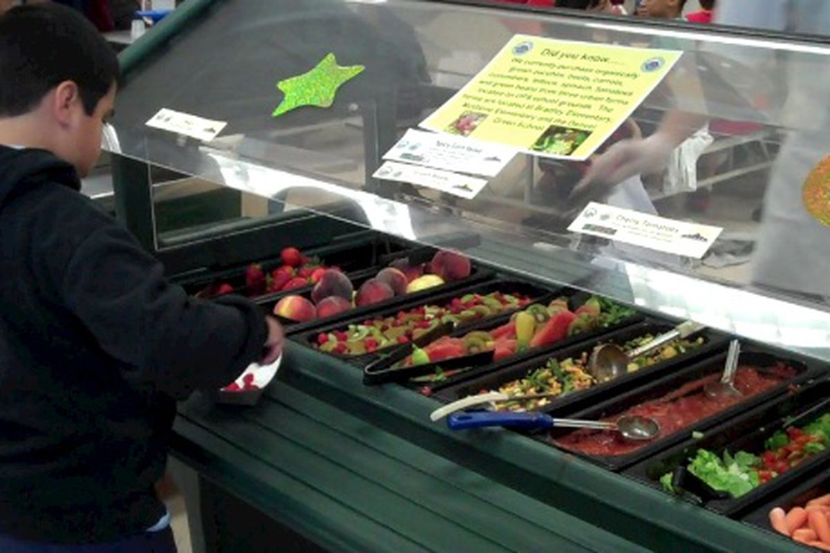 A student at Lowry Elementary chooses fresh fruit from his school's salad bar.