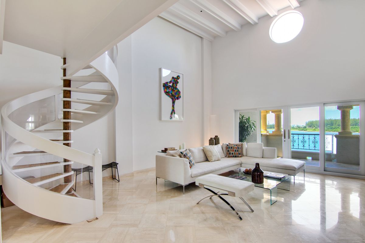 A spiral white staircase next to the living room, decorated with a white L-shaped couch, glass coffee table, white walls, and lightly-colored floors.