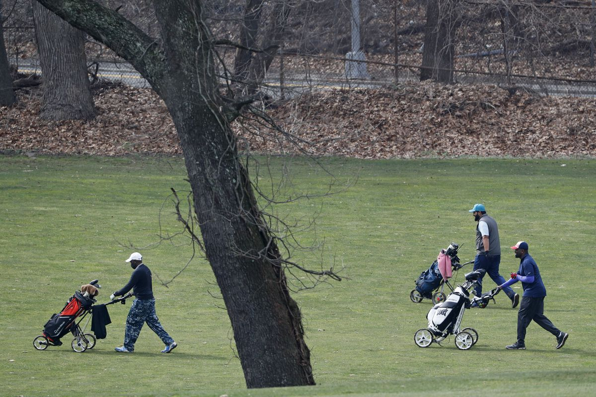 Golfers make their way down a fairway at Forest Park Golf Course in New York. Even as the pandemic has shuttered restaurants, bars and beaches, many golf courses around the country have managed to stay open with all sorts of precautions in place.