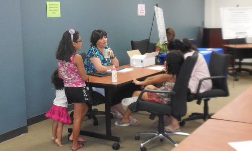 Lola Campos worked with a parent to fill out an application for free and reduced-price school meals.