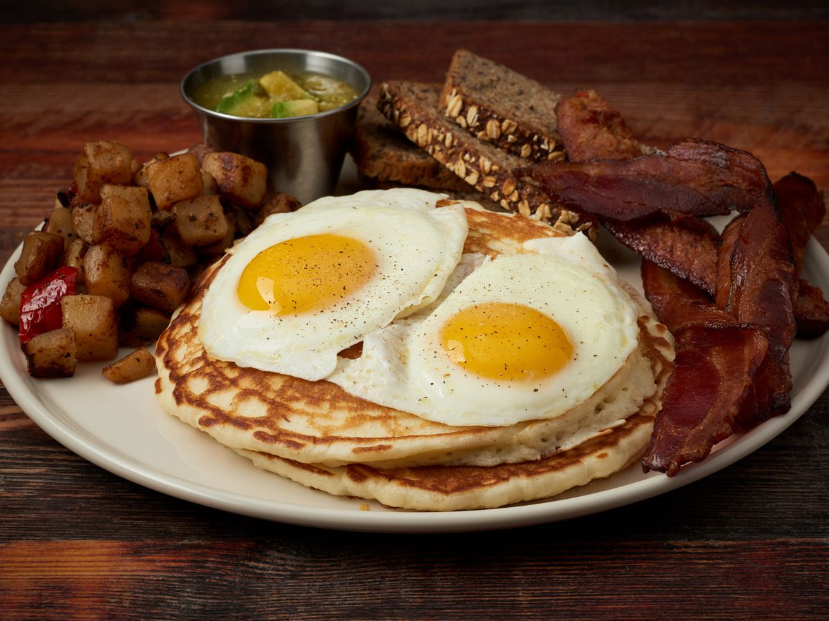 Pancakes and over-easy eggs with bacon and home fries