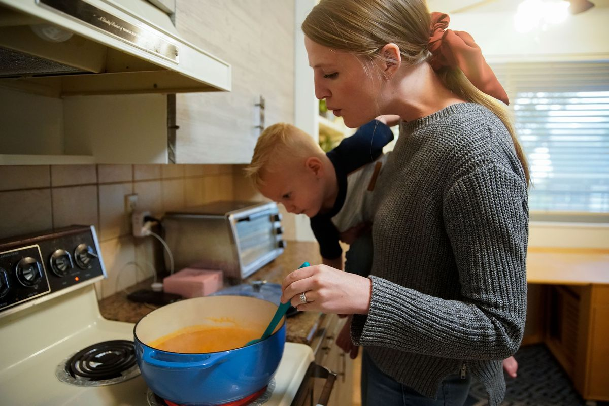 Elissa George prepares dinner for her family while carrying her son Tanner, 2, at their house in Provo on Friday, Oct. 8, 2021.