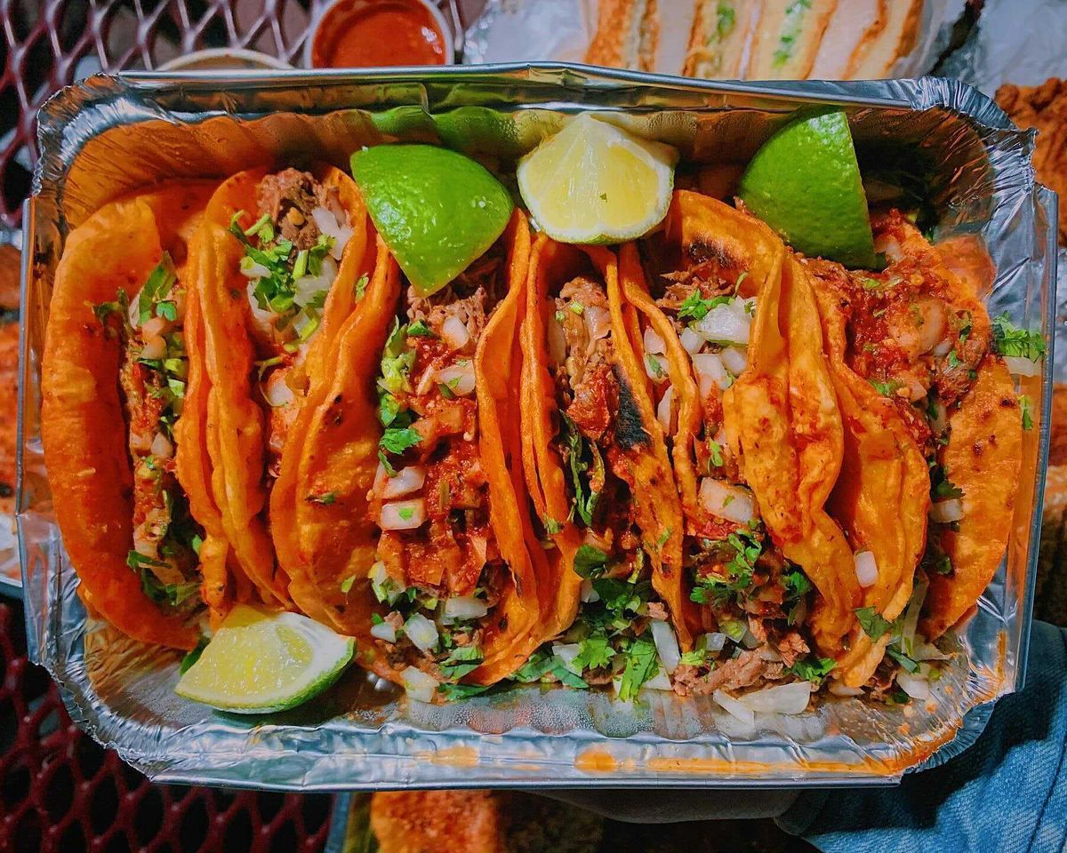 An overhead photograph of six brick-red tacos nestled in a takeout container. Each is double-wrapped in tortillas and stuffed with meat, onion, and cilantro, while wedges of lime dot the exterior.