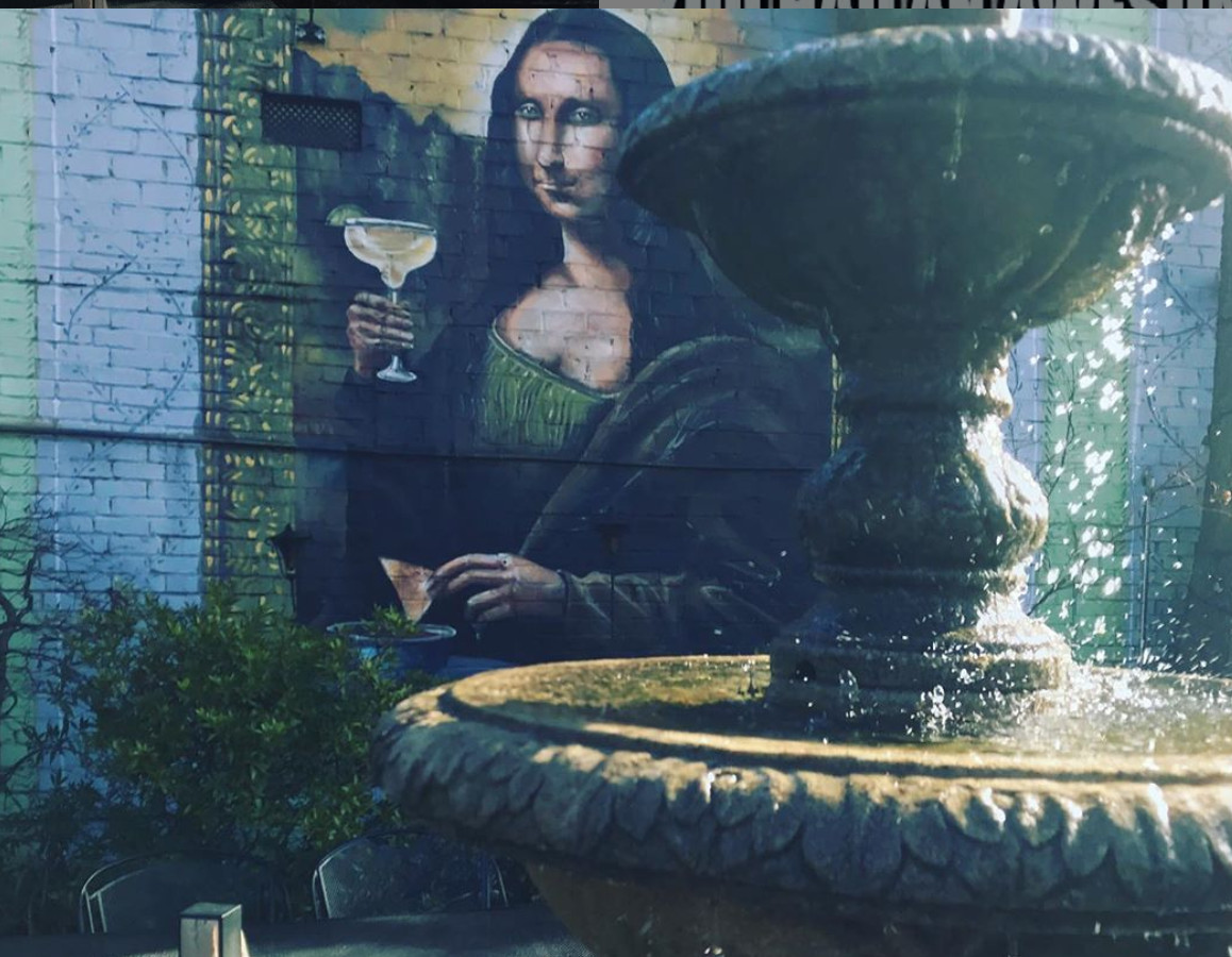 A fountain is in front of a mural of the Mona Lisa drinking a margarita.