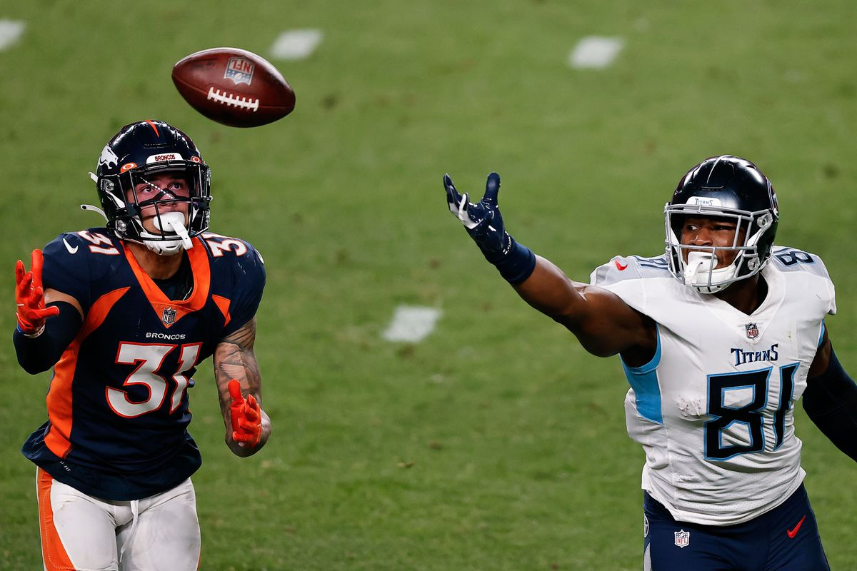 Denver Broncos free safety Justin Simmons attempts to grab a pass intended for Tennessee Titans tight end Jonnu Smith in the third quarter at Empower Field at Mile High.