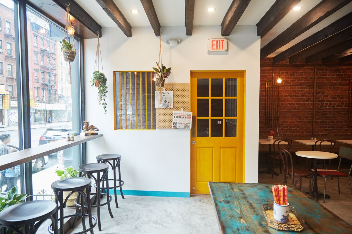 Potted plants hang from the ceiling in a naturally lit dining room with bar stools, high-top counters, and exposed brick.