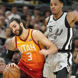 Utah Jazz's Ricky Rubio (3) collides with San Antonio Spurs' Dejounte Murray during the second half of an NBA basketball game Friday, March 23, 2018, in San Antonio. San Antonio won 124-120 in overtime. (AP Photo/Darren Abate)