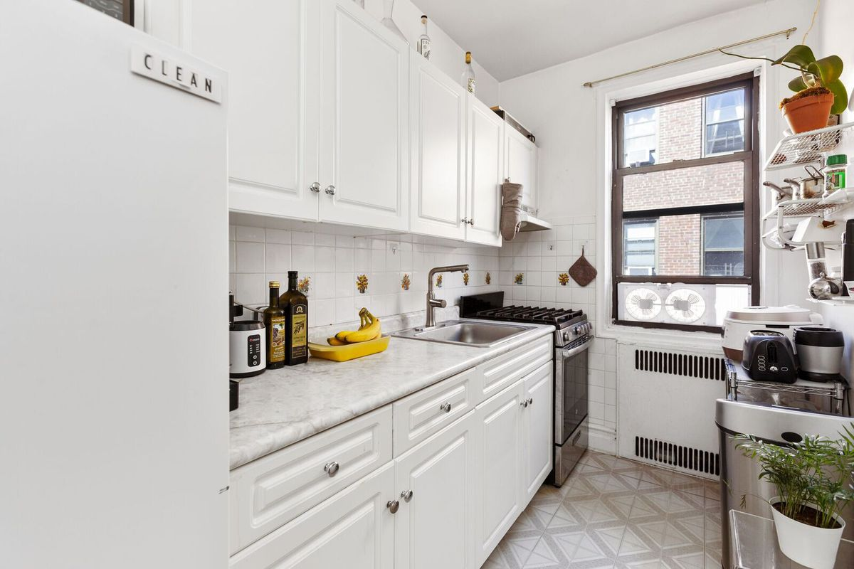 A kitchen with white cabinetry and a window.